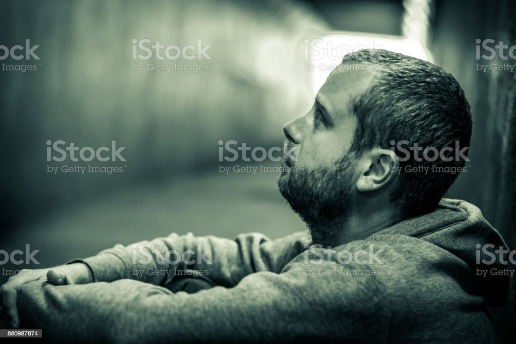 Profile close up view of young homeless caucasian male sitting in dark subway tunnel stock photo