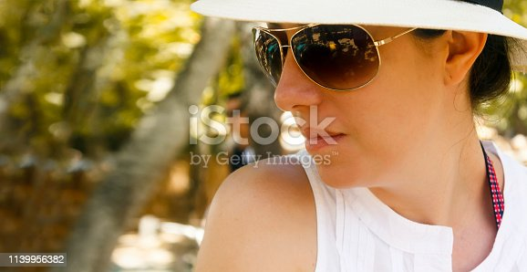 Profile close-up of beautiful woman with straw hat and sunglasses