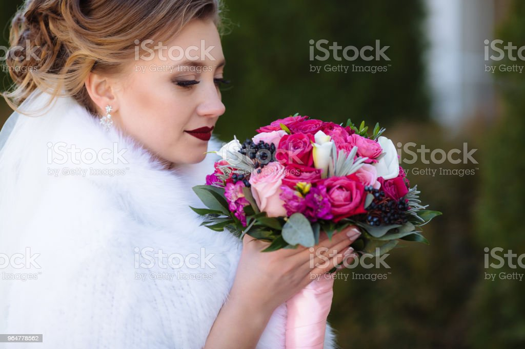 Profile close-up shooting bride admires a bouquet of flowers and breathes the aroma of roses. A girl with a delicate eye makeup and bright scarlet lips royalty-free stock photo