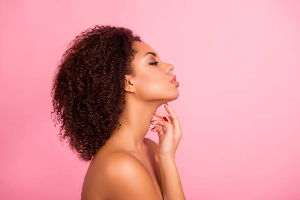 Profile, half face portrait of naked sensual, confident, attractive, brunette, charming, pretty enjoying her perfect skin with close eyes, touching her neck with fingers, isolated on pink background stock photo