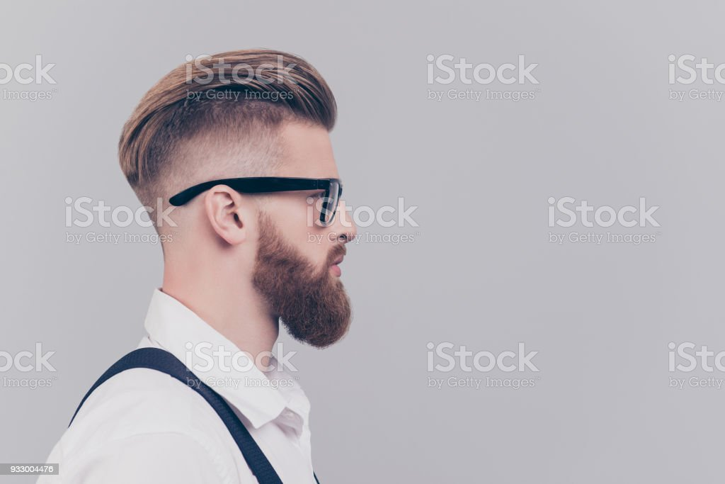 Profile half-faced side view portrait of serious confident concentrated attractive manager with blonde hair wearing rimmed glasses white shirt black suspenders isolated on gray background empty blank stock photo