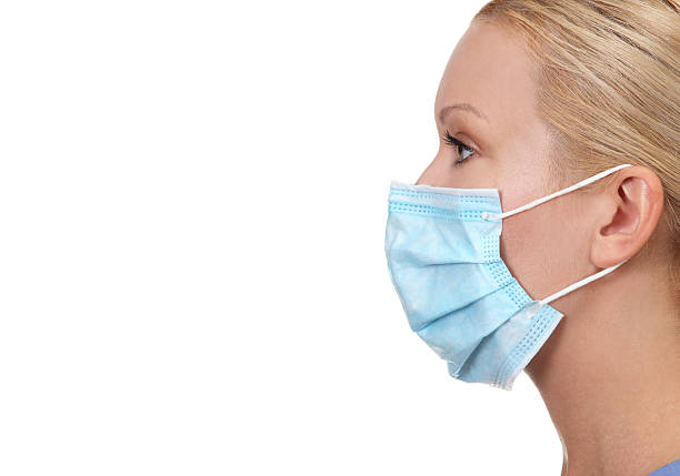 Profile image of young female nurse Profile image of young female nurse wearing face mask isolated on white surgical mask stock pictures, royalty-free photos & images