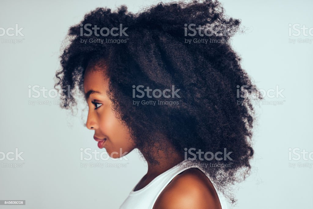 Profile of a cute little African girl with curly hair royalty-free stock photo