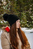 Profile of a girl in the winter forest. The girl is sad about the summer and the sun.