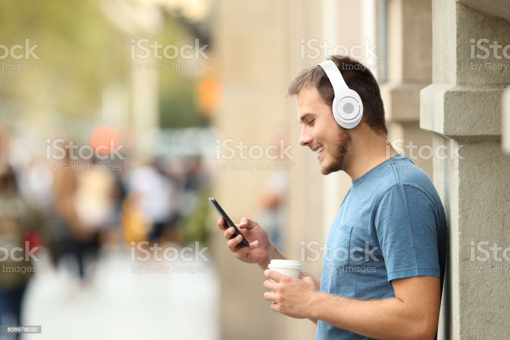 Profile of a guy listening music on line on the street stock photo