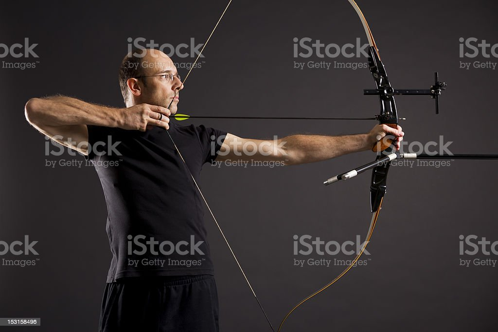 Profile of a man dressed in black aiming a bow and arrow  stock photo