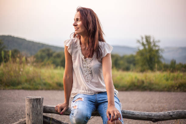 Profile of a mature woman sitting on a wooden fence in nature stock photo