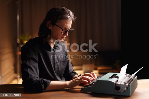 Image of a man with long hair in eyeglass, seated at a wooden table, working on a old vintage typewriter in darkness interior. Copy space.