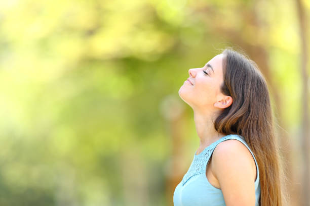 Profile of a woman breathing fresh air in a forest stock photo
