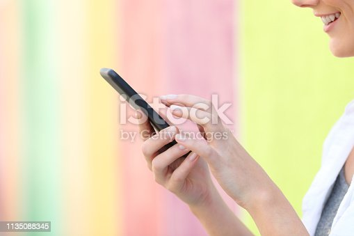 istock Profile of a woman hand using cell phone in a colorful street 1135088345