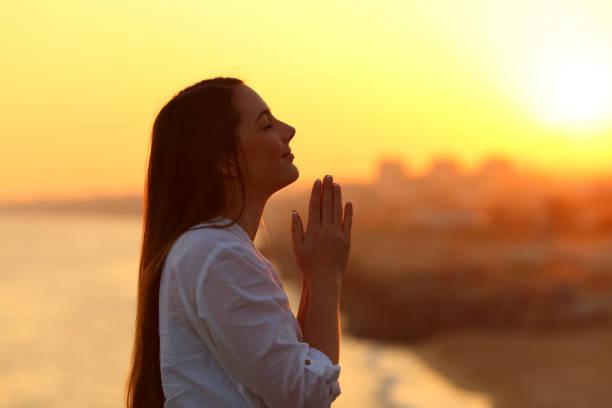 profil kobiety modlącej się o zachodzie słońca - bóg zdjęcia i obrazy z banku zdjęć