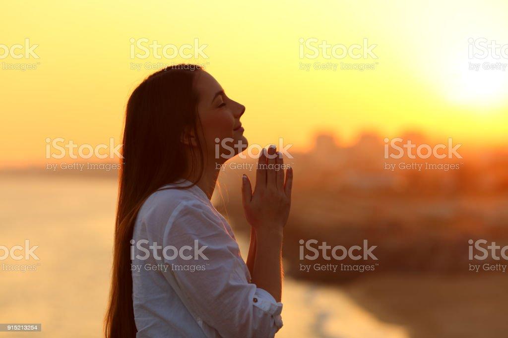 Profile of a woman praying at sunset stock photo