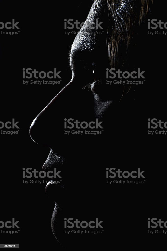 Profile of a young Caucasian male face in the dark stock photo