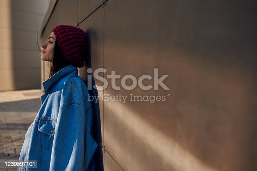 istock Profile of a young female leaning back on a wall outdoors 1239597101