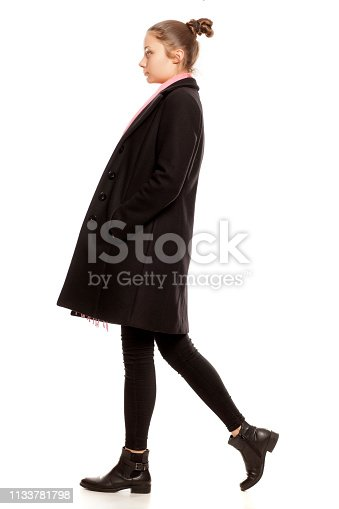 profile of a young girl in winter clothes posing on a white background