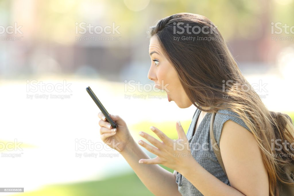 Profile of an amazed woman using a phone stock photo