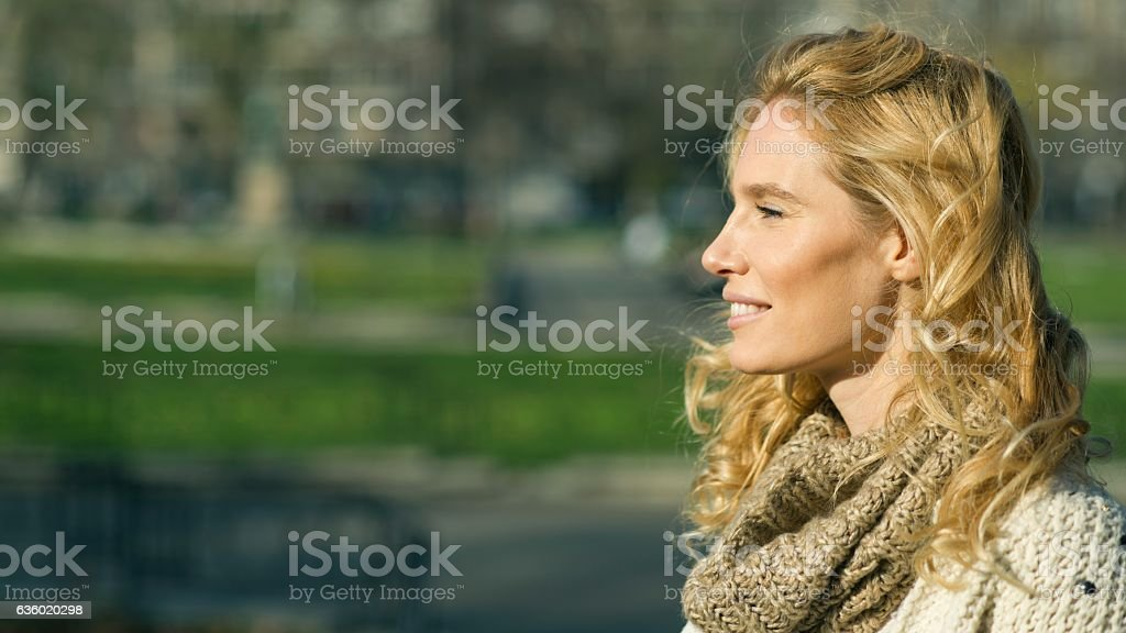 Profile of an beautiful blondy smiling woman looking away stock photo