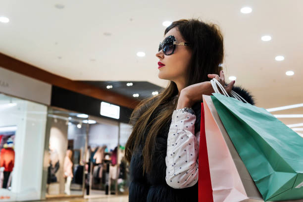 profil der attraktiven dame in brille und pelzweste hält viele einkaufstaschen auf mall hintergrund. mädchen mit paketen zu fuß im kaufhaus. zufriedenheit nach ausfungen fühlen. sideview. - geld schön verpacken stock-fotos und bilder