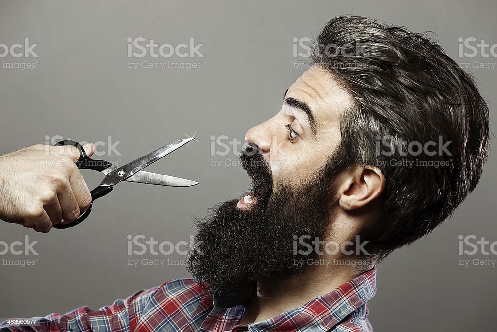 Profile of bearded man scared by scissors and moving back stock photo