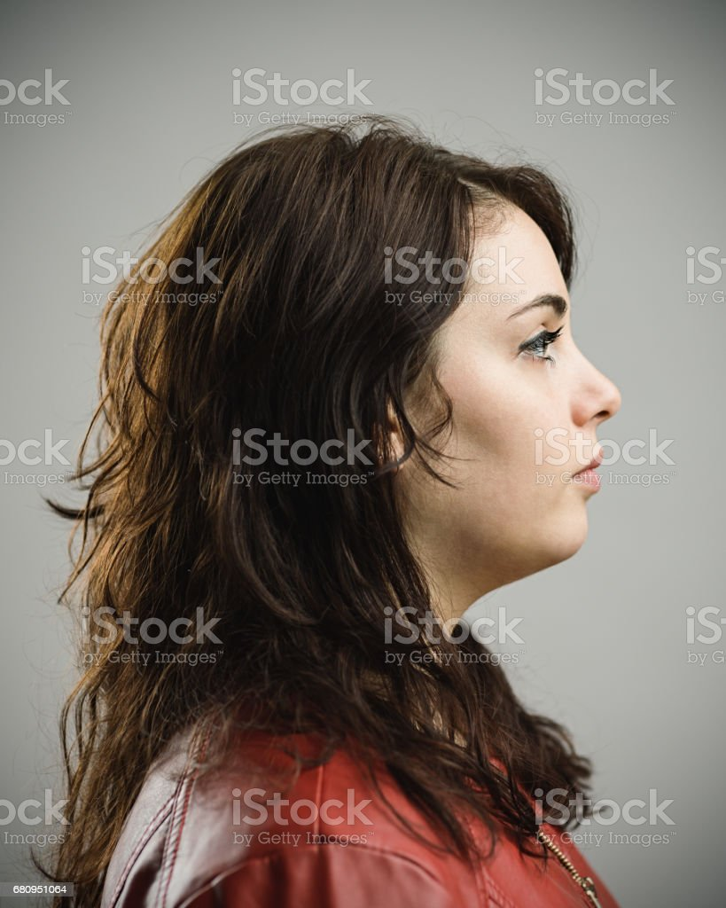 Profile of beautiful young woman against gray background royalty-free stock photo