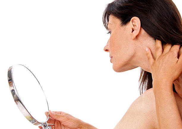 Profile of brunette woman examining jawline in a hand mirror stock photo