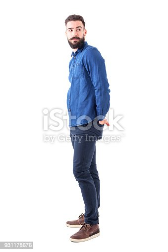 931173966istockphoto Profile of cool young trendy man in blue denim shirt looking back over the shoulder. 931178676