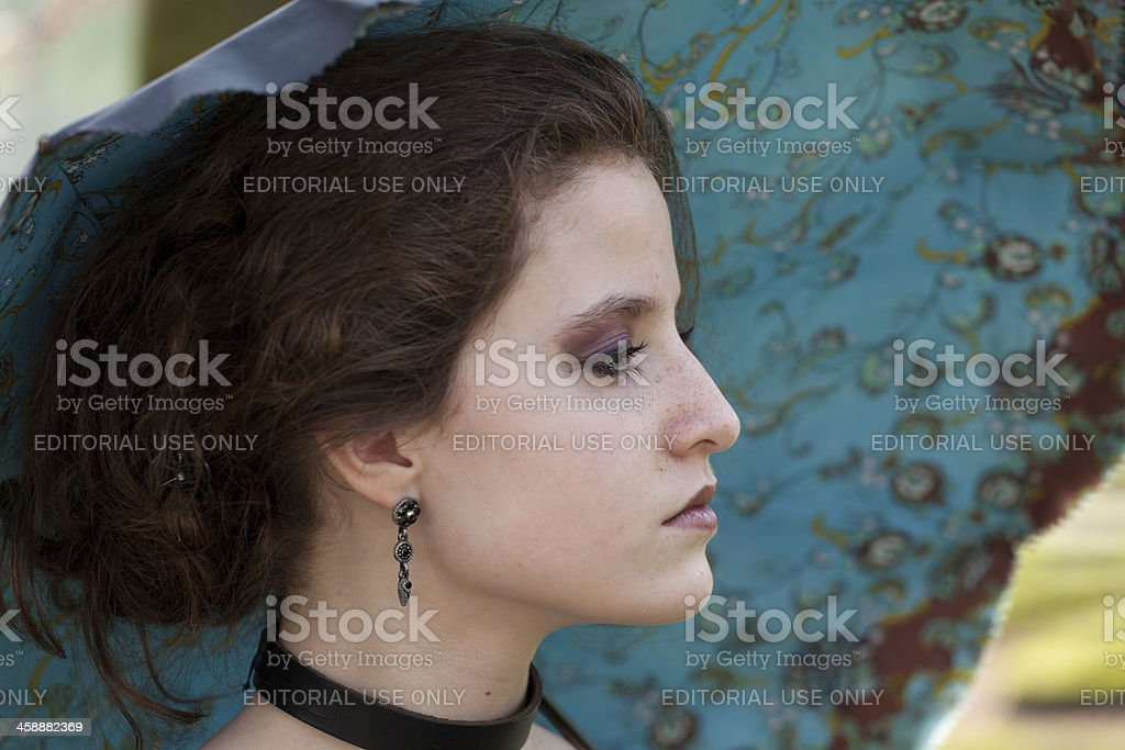 Profile of dressed up woman with umbrella at Fantasy Fair foto