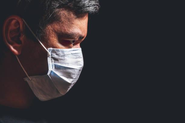 profil des mannes in maske - pandemie stock-fotos und bilder