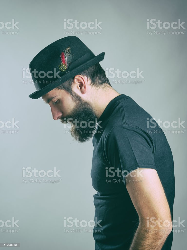 Profile of sad hunched bearded man with hat looking down stock photo