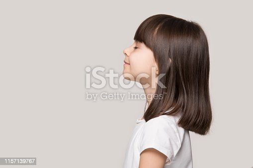 Profile side view face brown-haired little girl standing isolated on beige studio background, preschool kid do deep breath enjoy fresh air or dreaming fill with energy feeling healthy and good concept