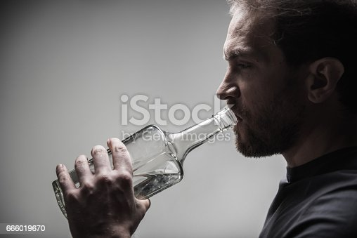 istock Profile of serious man while holding big bottle 666019670