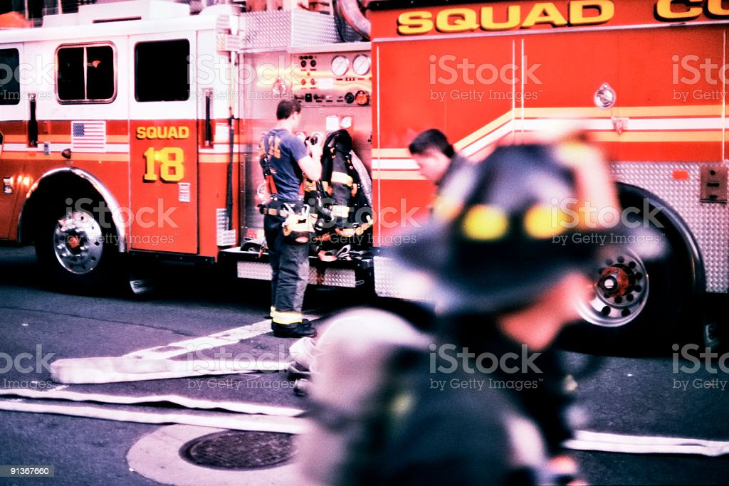 Profile of Squad 18 red fire truck with firemen around royalty-free stock photo