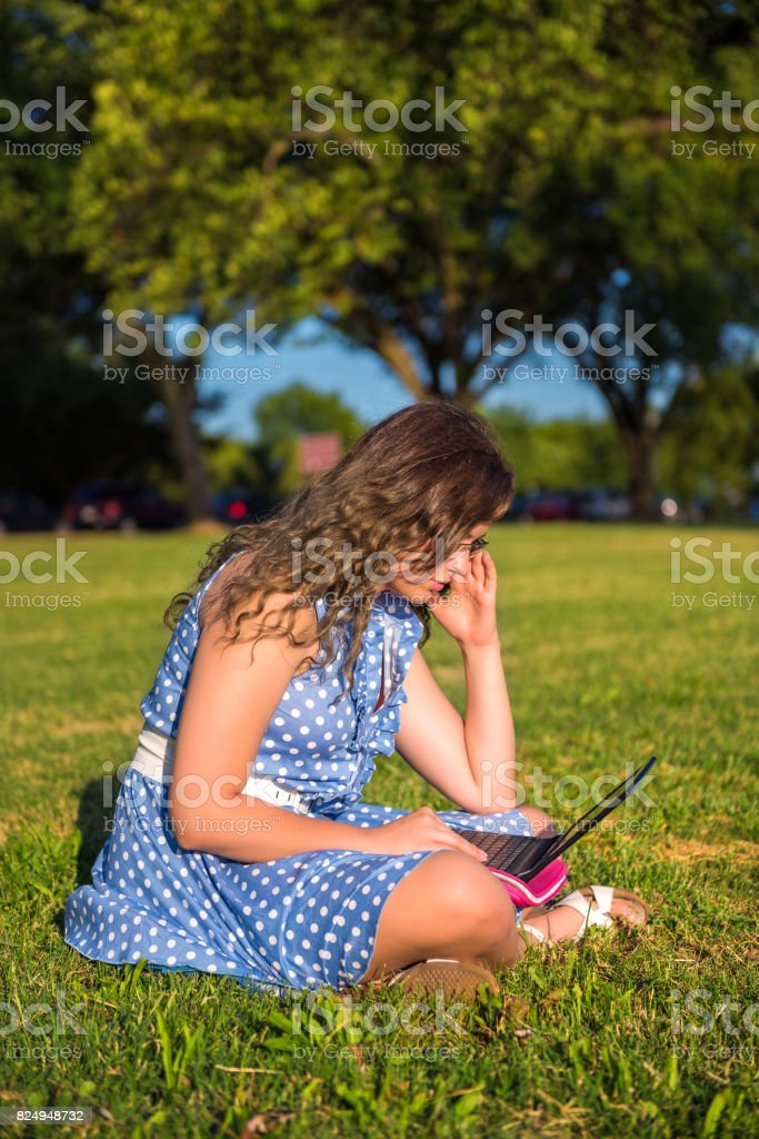 Profile Of Student Young Woman Sitting In Green Grass Park Hunched