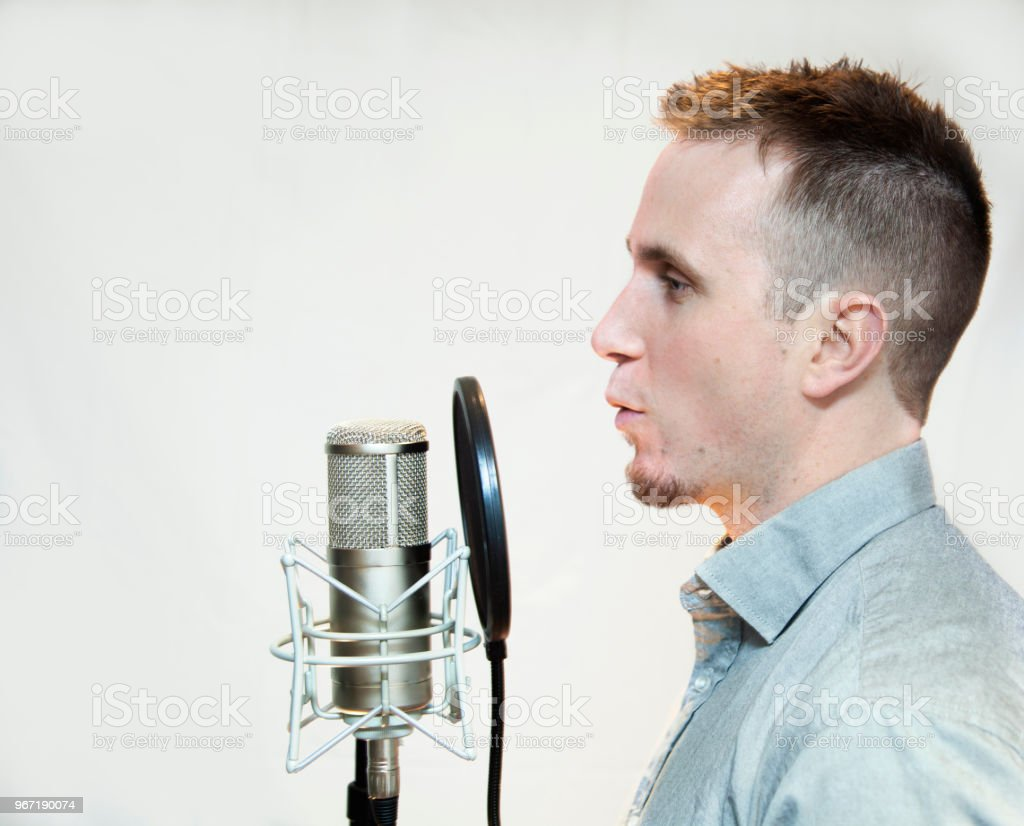 Profile of young man speaking into microphone doing voice over work