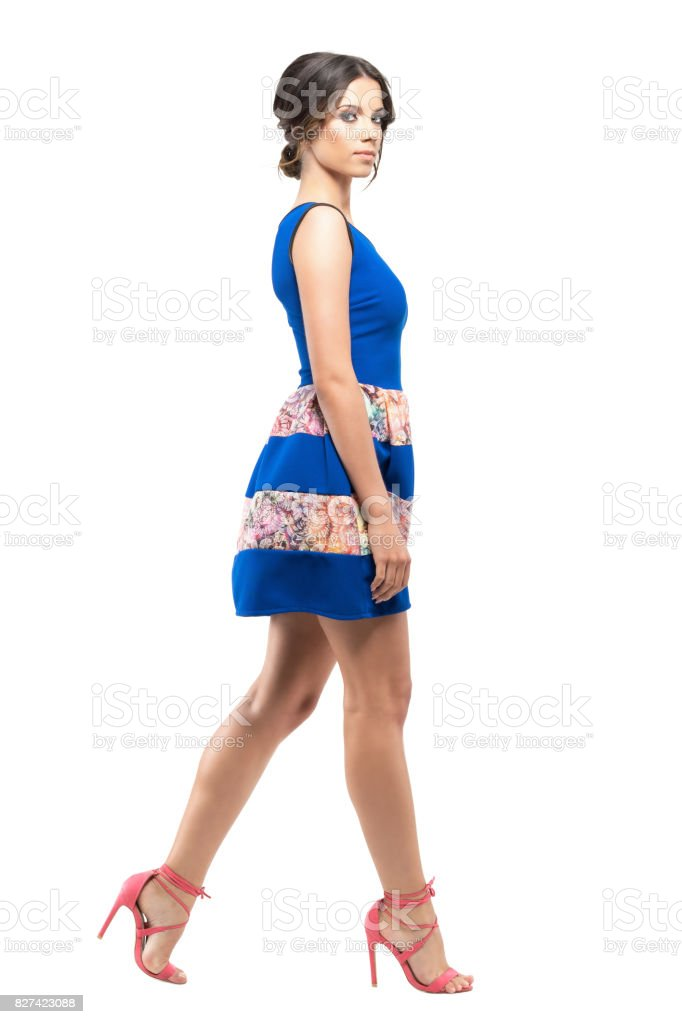 Profile of woman in short summer sleeveless dress walking and looking at camera. stock photo