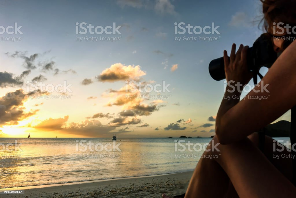 Profile of woman photographer with DSLR camera on the beach at sunset stock photo