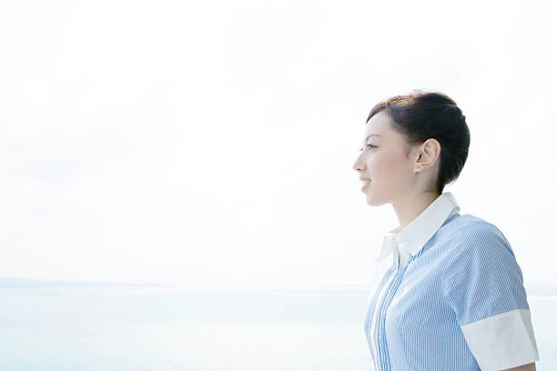 プロフィールの笑顔の女性彼女の背中を青い海 - 女性 横顔 日本人 ストックフォトと画像