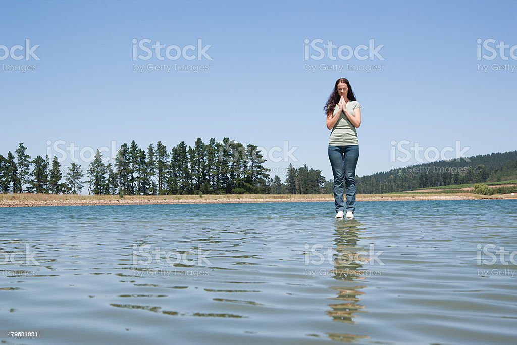 Profile of woman standing on water praying stock photo