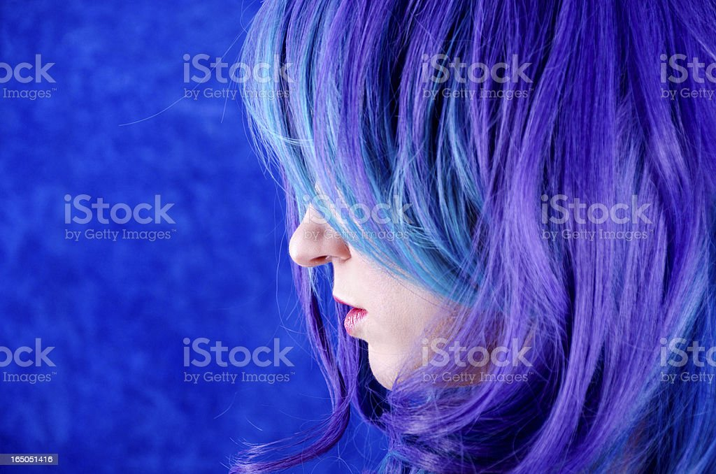Profile of woman with blue/purple hair over upper face. stock photo