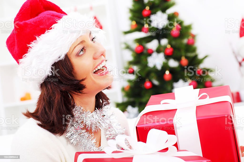 Profile of woman with presents, behind her Christmas tree. royalty-free stock photo