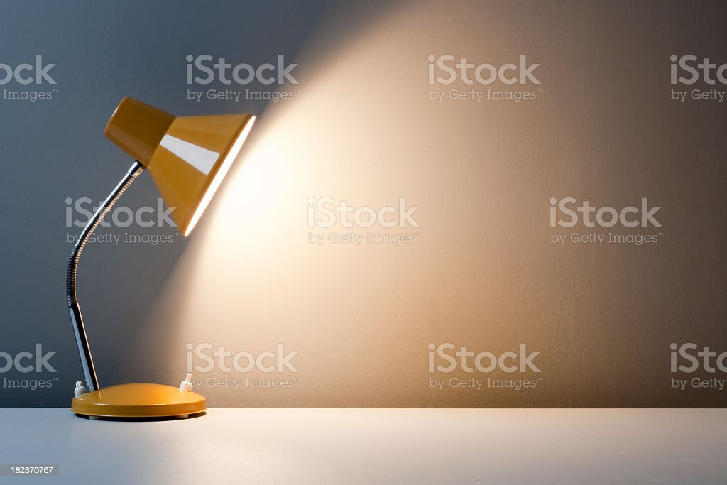 Profile of yellow desk lamp, turned on on white table royalty-free stock photo