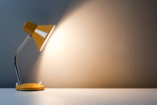 Profile of yellow desk lamp, turned on on white table stock photo