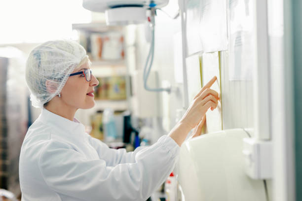 Profile of young Caucasian blonde female employee reading schedule on the wall while standing in food factory. Profile of young Caucasian blonde female employee reading schedule on the wall while standing in food factory. hair net stock pictures, royalty-free photos & images