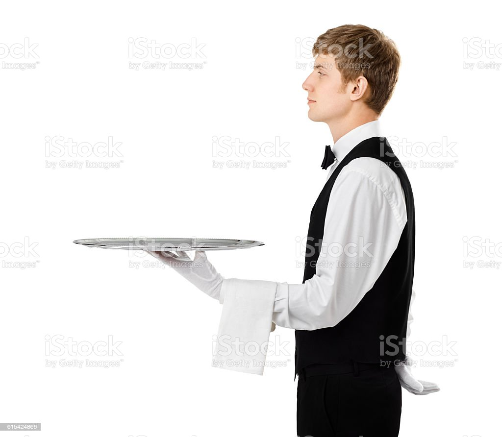 Profile of young handsome waiter holding empty tray stock photo