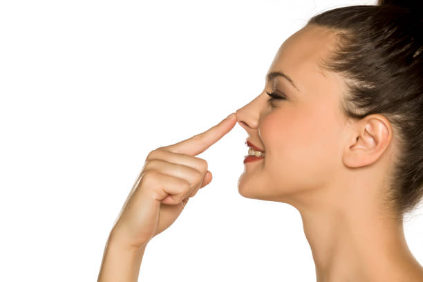 profile of young happy woman touches her nose with her finger on a white background stock photo