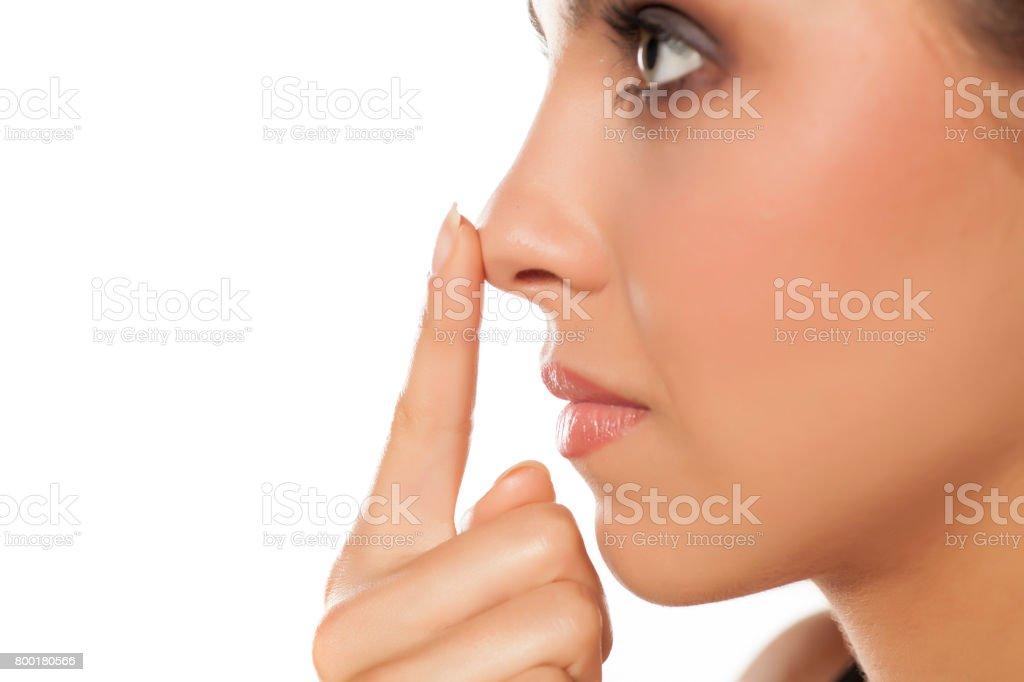 設定檔的年輕女人摸她的鼻子 - 免版稅20多歲圖庫照片