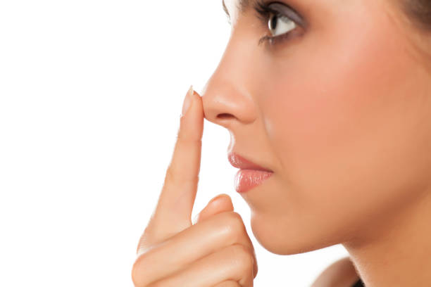 Profile of young woman touching her nose stock photo