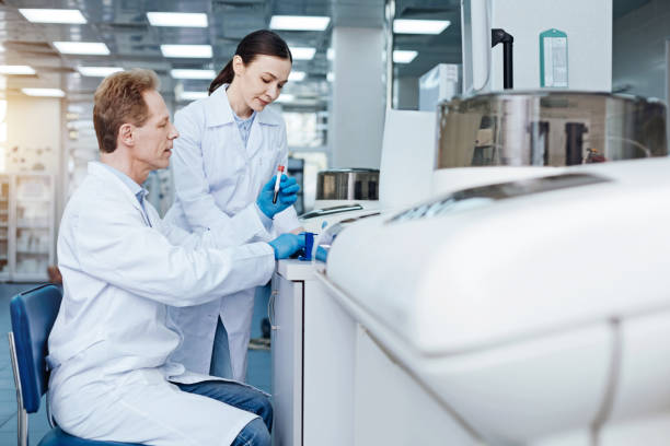 Profile photo of male practitioner sitting at his workplace Look here. Amazing young researcher bowing her head and looking downwards while standing near her assistant dna purification stock pictures, royalty-free photos & images