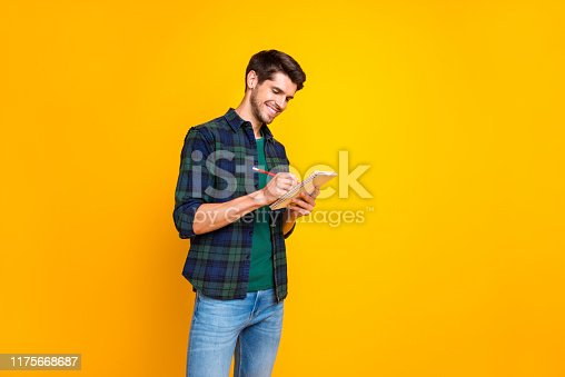 1175668510 istock photo Profile photo of nice guy with organizer in hands making notes creating startup idea wear casual checkered shirt and jeans isolated yellow color background 1175668687