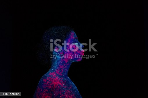 Profile portrait of a beautiful girl alien. Ultraviolet body art blue night sky with stars and pink jellyfish, Girl blowing to in front of.